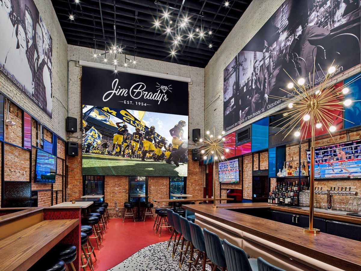 A screen airing U-M football hangs below a sign for Jim Brady's in a room full of TVs, long bars, communal tables, and Sputnik lights.