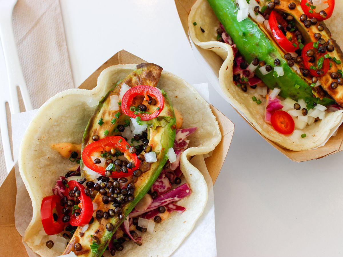 A pair of seared avocado tacos at Whole Heart Provisions sit atop a white table.