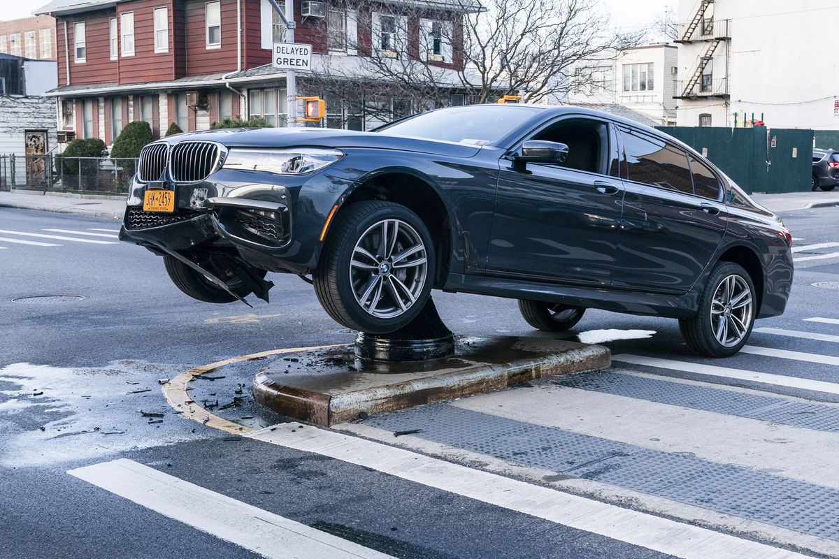 A car in the middle of a paved road stuck with its front wheels off the ground atop a median strip.