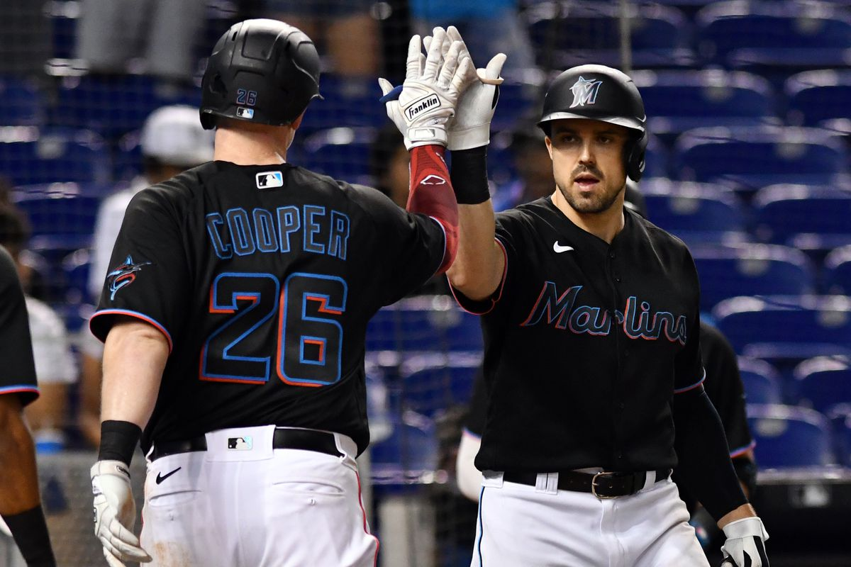 Miami Marlins first baseman Garrett Cooper (26) is congratulated by Miami teammate Adam Duvall (14) after hitting a two-run home run in the eighth inning against the Washington Nationals at loanDepot Park