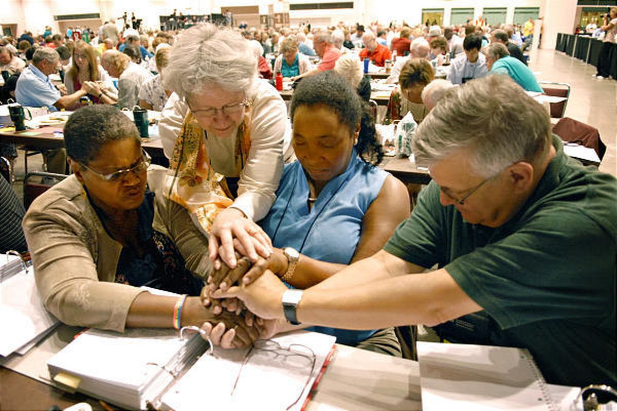Pastor Orinda Hawkins-Brinkley, left, Diane Yeager, Marj Ellis and Steven Schnittke stop for a moment of prayer Friday during the Evangelical Lutheran Church in America assembly at the Minneapolis Convention Center.