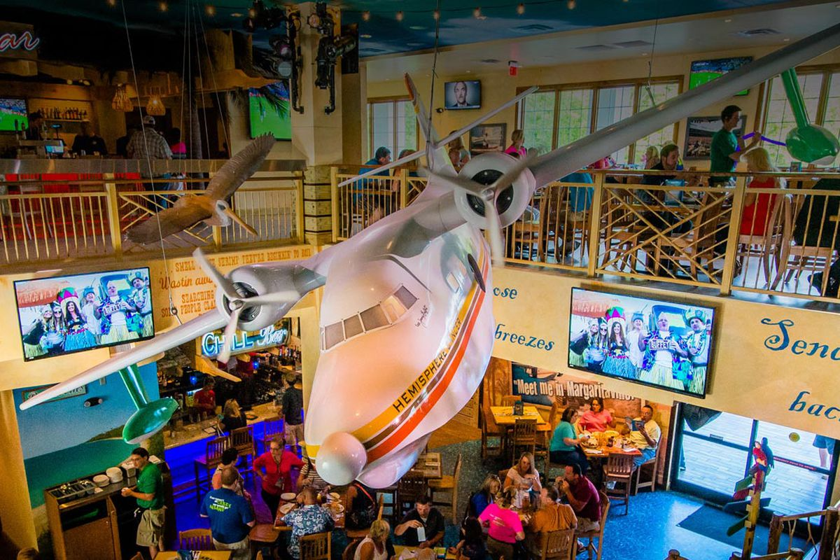 Restaurant interior featuring kitschy island decor. Neon signage denotes a tiki bar in one portion of the restaurant, and a giant helicopter hangs from the ceiling.