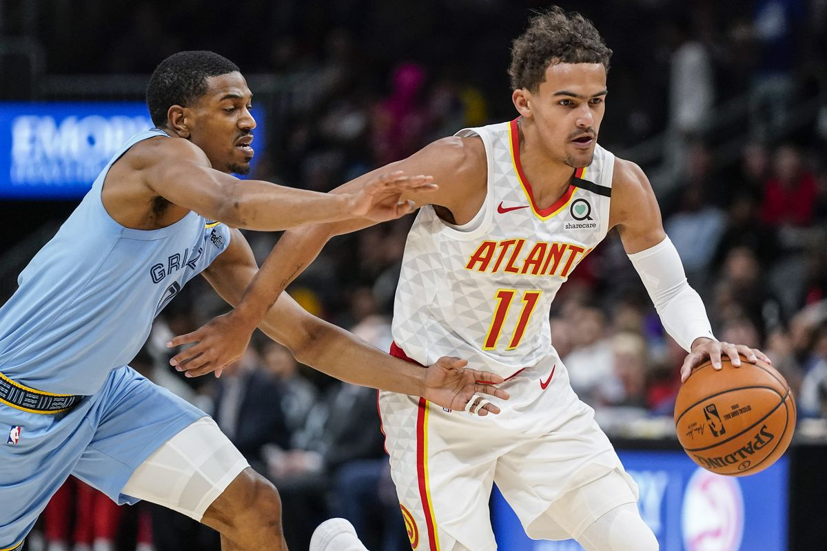 Atlanta Hawks guard Trae Young dribbles the ball past Memphis Grizzlies guard De'Anthony Melton during the first quarter at State Farm Arena.