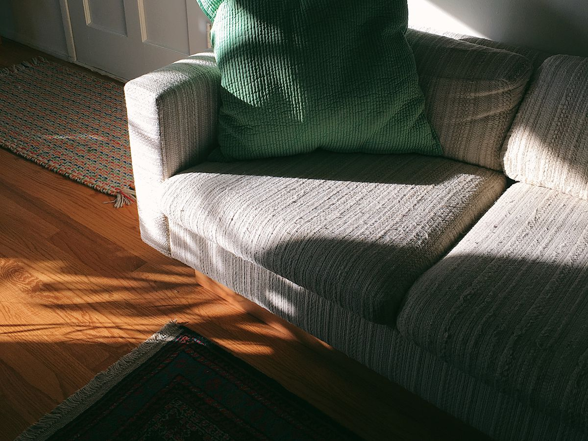 Sunlight and shadows appear over a gray sofa with a small green pillow.