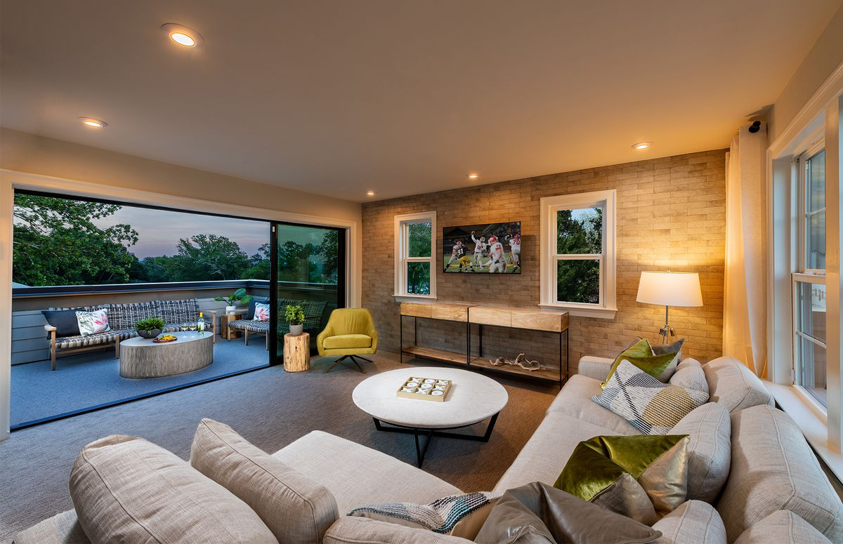 A cozy living area with a nearly full-wall window opening up to an outdoor patio.