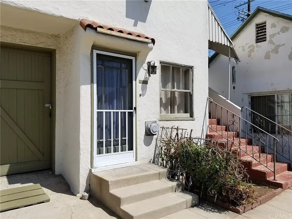 Outside view of apartment entrance with stairs on the side.
