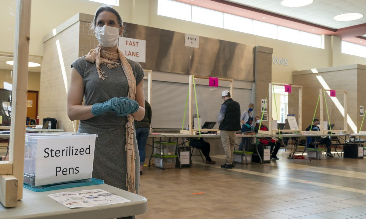Poll worker Rhonda Griffin stands ready to hand out sterilized pens at a polling place on April 7, 2020 in Sun Prairie, Wisconsin.