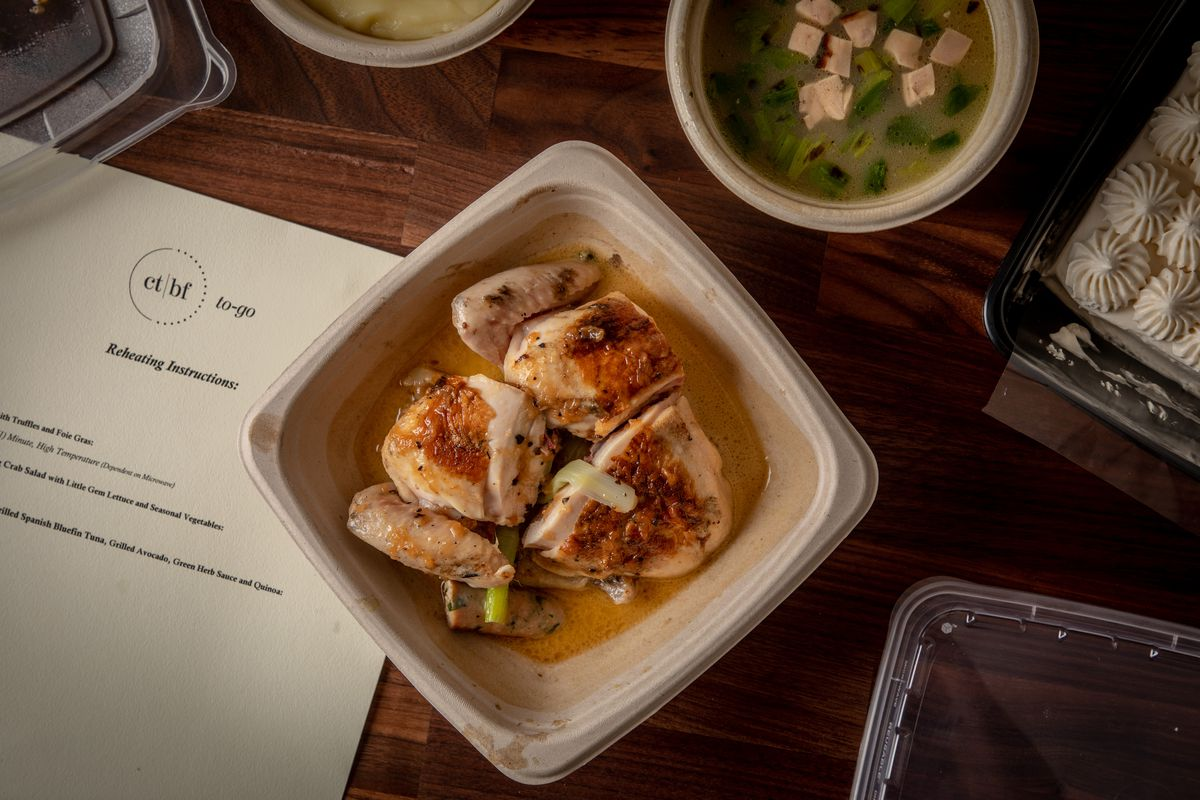 Chicken in a takeout container on a wood surface