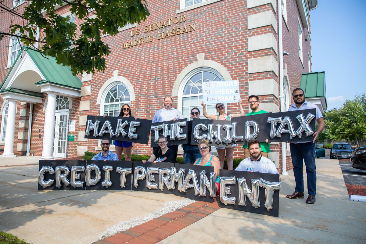 """Protesters hold signs that read """"Make the child tax credit permanent."""""""