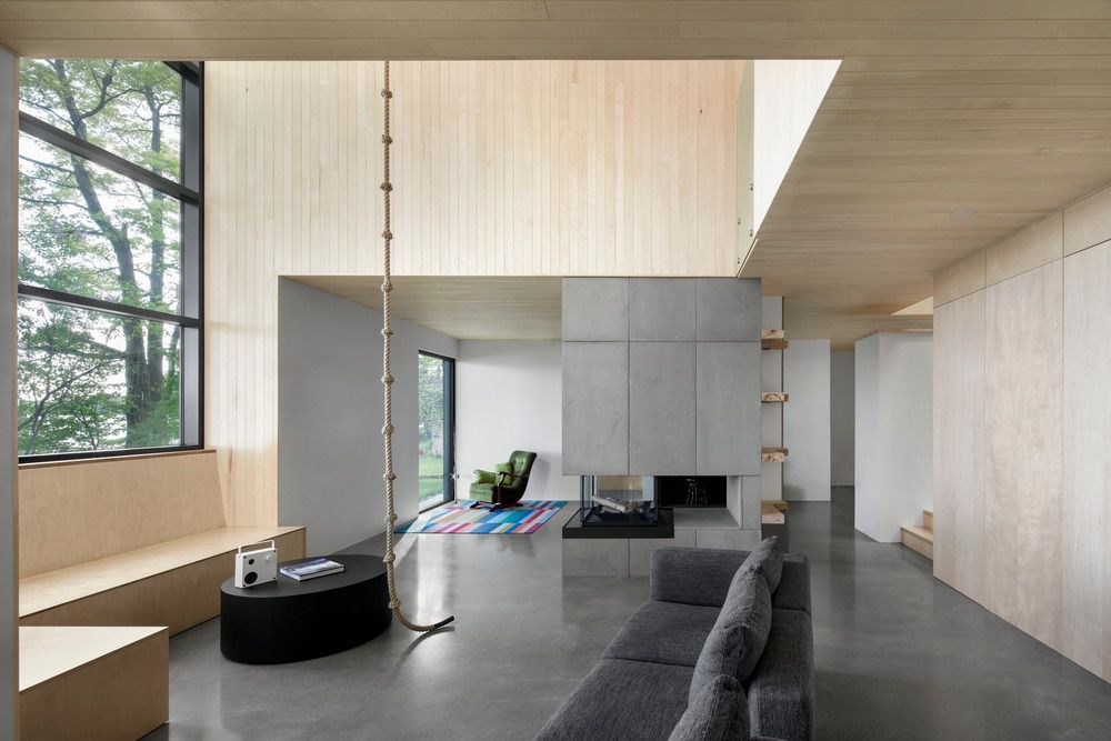 Rope hanging from atrium ceiling in an open living area with concrete floors and gray sofa.