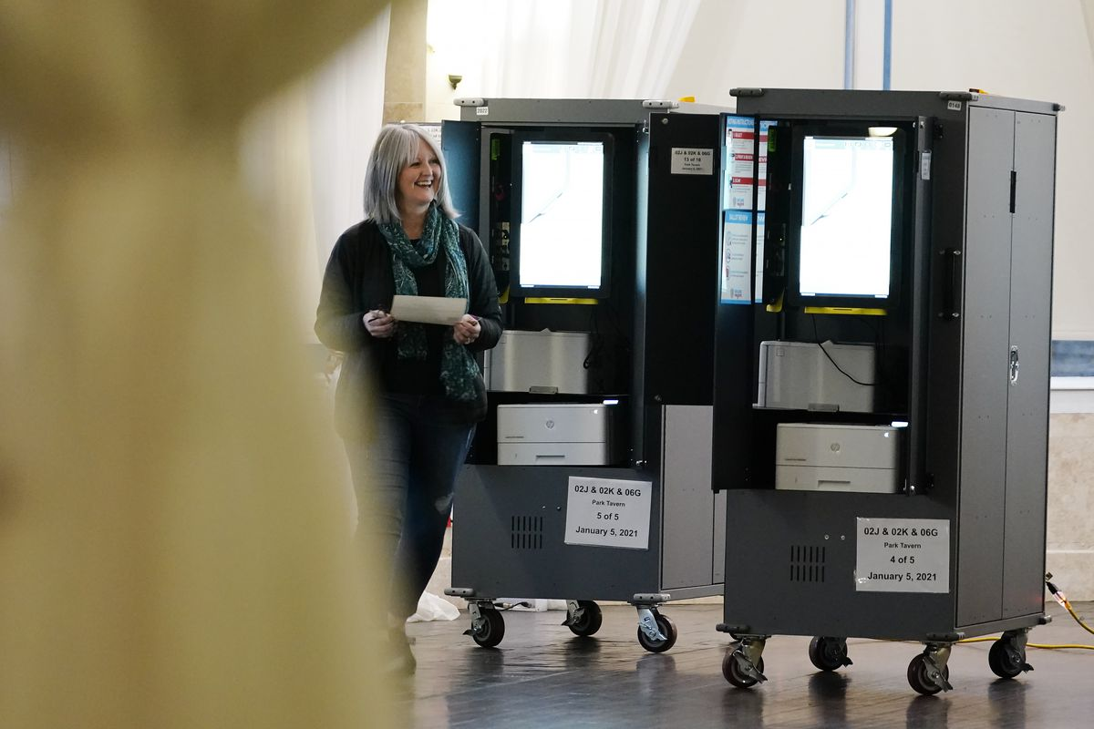 A vote walks away after casting their ballot in Georgia's Senate runoff election on Tuesday, Jan. 5, 2021, in Atlanta. (AP Photo/Brynn Anderson)