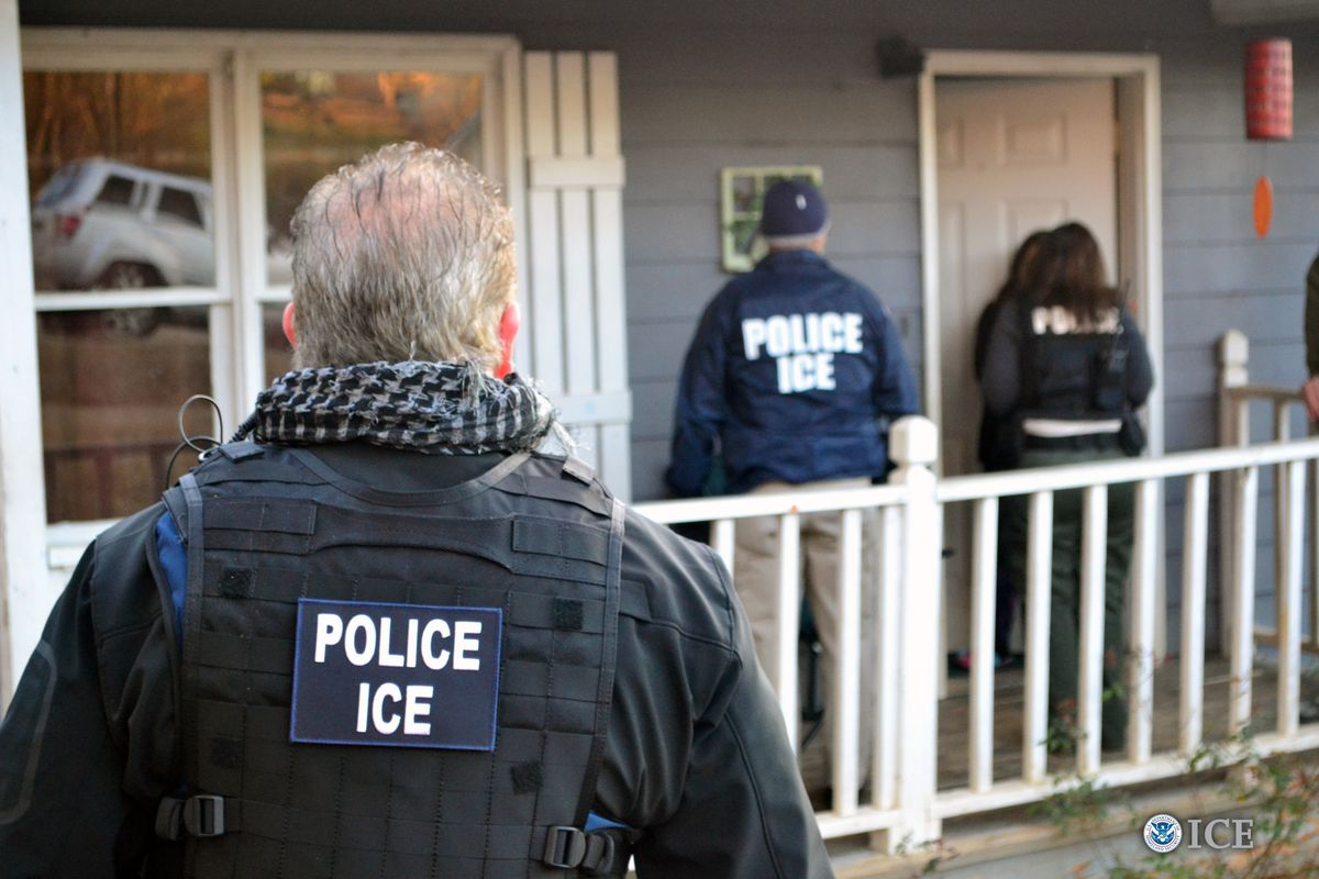 """Three agents with """"Police ICE"""" jackets prepare to enter the front door of a residential property."""