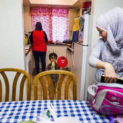 Nour Bilal, 15, puts away her homework while her mother, Kholoud Abou Arida, prepares dinner and her brother, Zain Bilal, 3, plays at their home in Millcreek on Tuesday, Sept. 8, 2015.