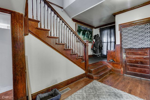A staircase and front door with original wood.