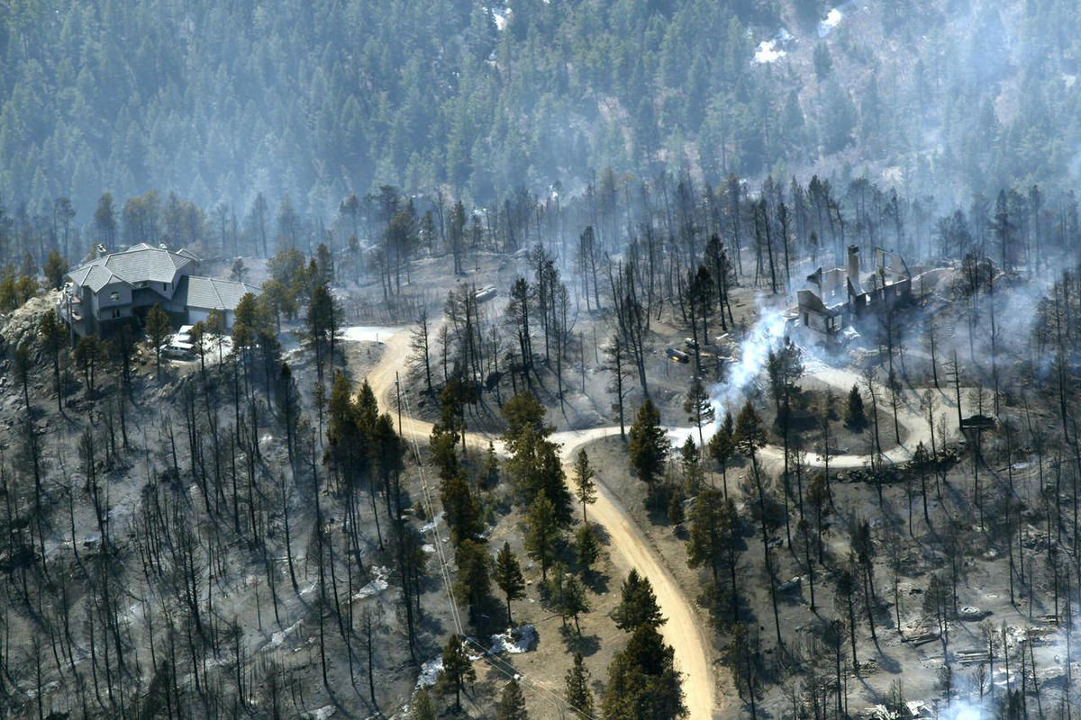 FILE - In this March 27, 2012 photo, one home stands untouched at left while another home at right smolders after burning in the Lower North Fork Wildfire in the foothills community of Conifer, Colo., southwest of Denver. Emergency officials told confused