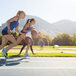 BYU track athletes Whittni Orton, right, and Anna Camp-Bennett run a mile race while dribbling a basketball on Sept. 4.