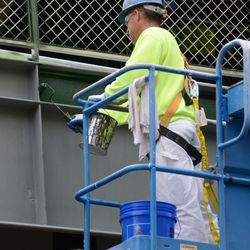 3:30 p.m. Painting the back of the bleachers behind the right-field patio -
