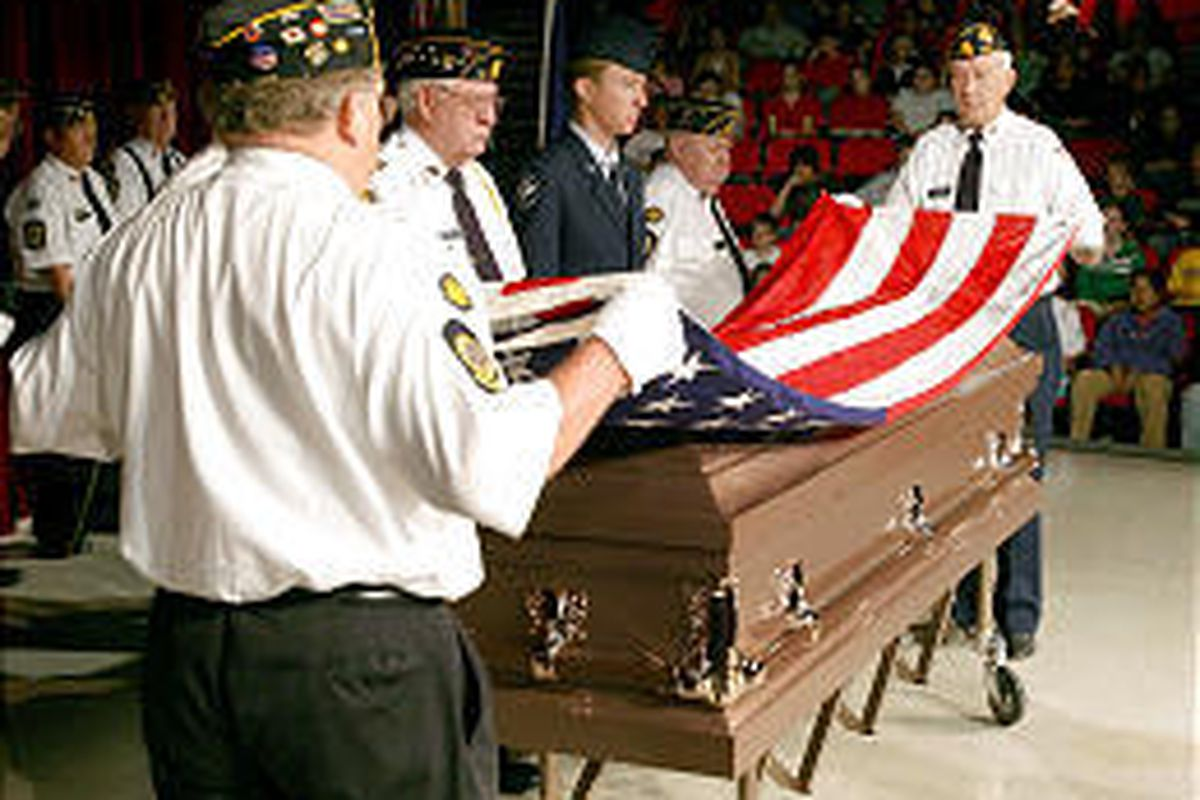 Burt Gividen, left, and Pete Workman fold the flag with other members of the American Legion during an assembly in Orem.