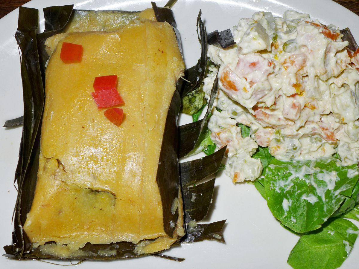 A venezuelan tamale unfolded from a banana leaf with salad on the side