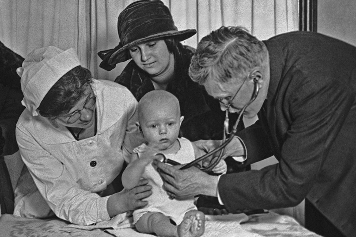 A baby is examined in 1915.