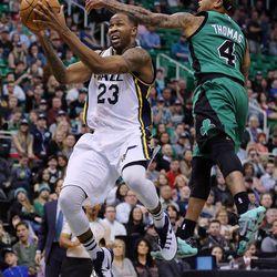 Utah Jazz forward Chris Johnson (23) shoots with Boston Celtics guard Isaiah Thomas (4) defending during NBA basketball in Salt Lake City, Friday, Feb. 19, 2016.