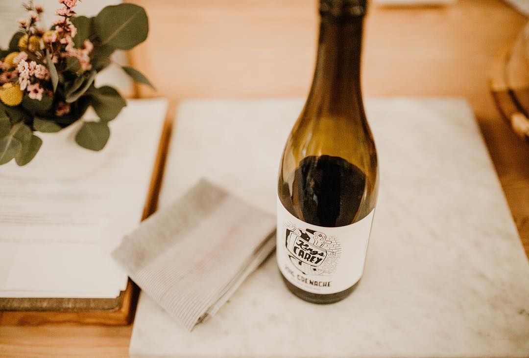 A bottle of Kings Carey wine on a wooden table.