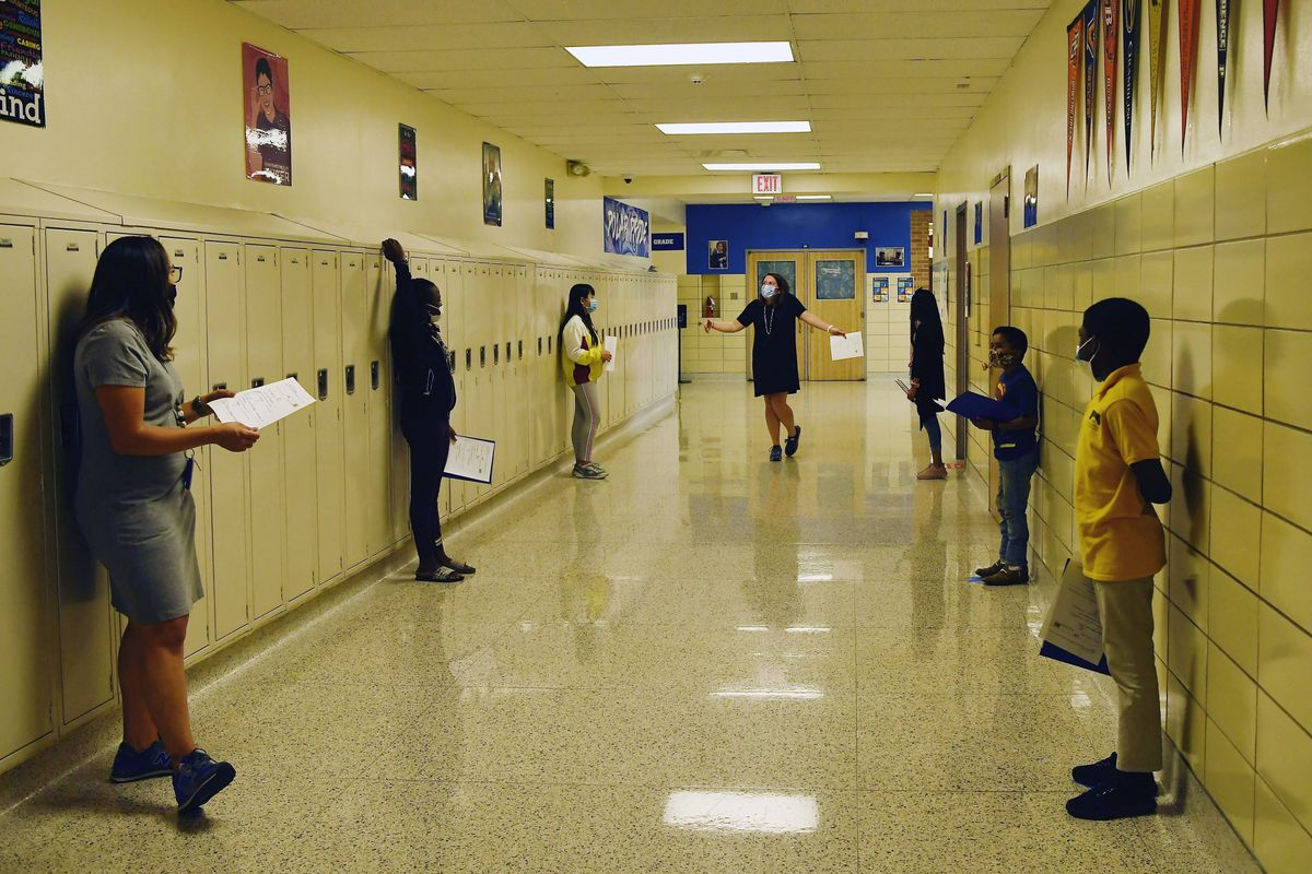 Middle school students are spaced out in a hallway with lockers, during a conversation exercise.