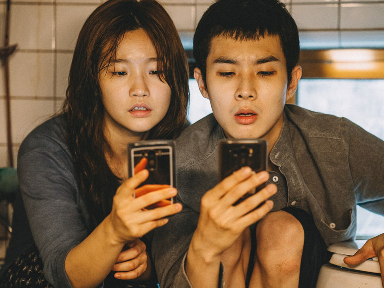 """Park So-dam and Choi Woo-sik sit close to one another on the floor of a bathroom while each stares at their phone in the movie """"Parasite."""""""