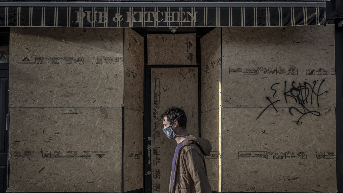 A man in a mask walks past Brooklyn Public House, which has been boarded up with plywood