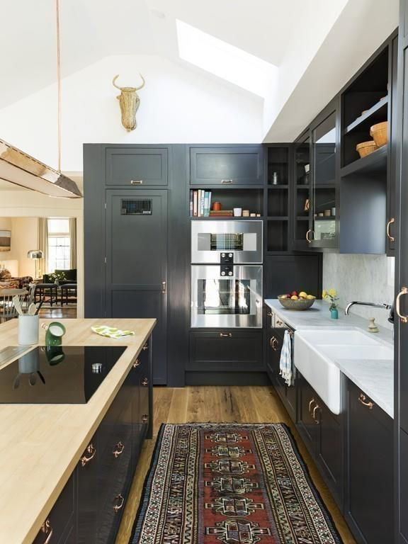 A kitchen with a long counter and a bank of cabinetry that includes the oven.