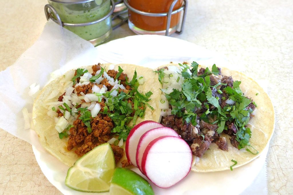 Two corn tortilla tacos on a white plate with red and green salsa in the background.