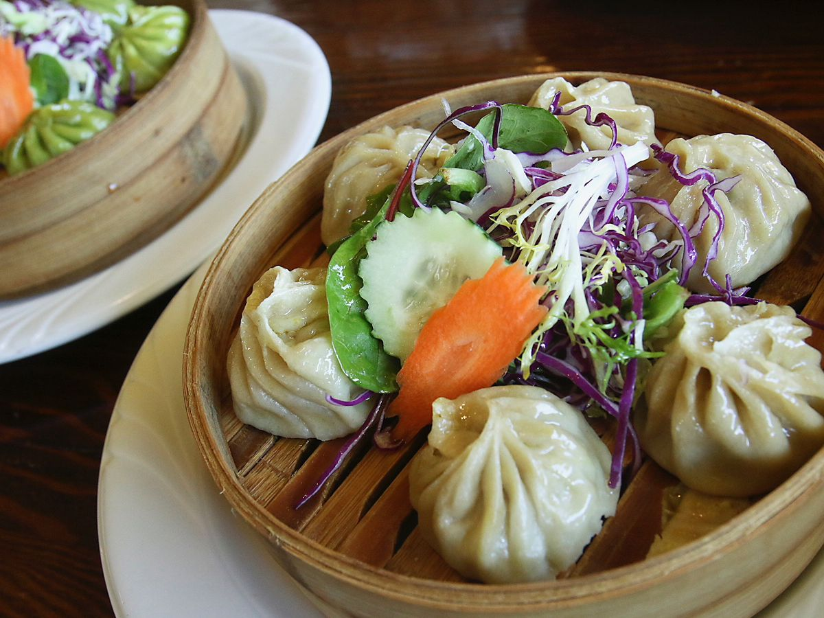 Steamers of momos topped with vegetable garnish
