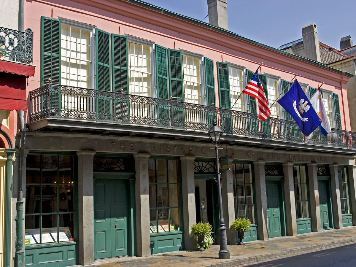 The facade of the Historic New Orleans Collection. There are green doors and shutters. The outer wall is pink.