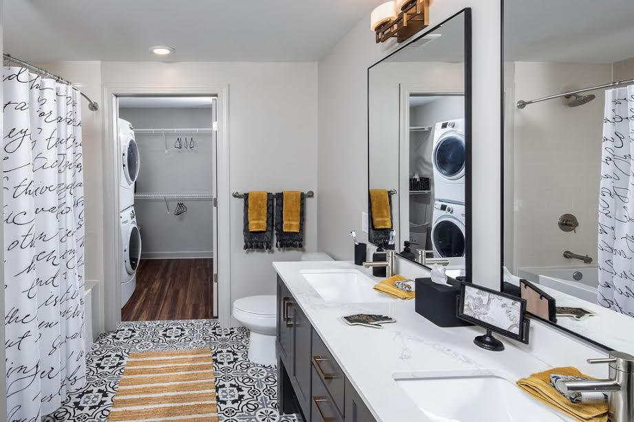 A white master bathroom with two sinks.