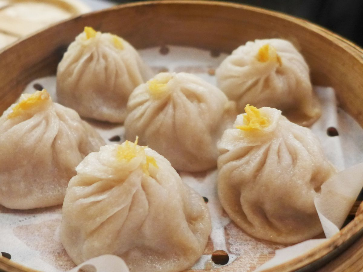 Six purse shaped dumplings with a pucker and wad of orange crabmeat at the top.