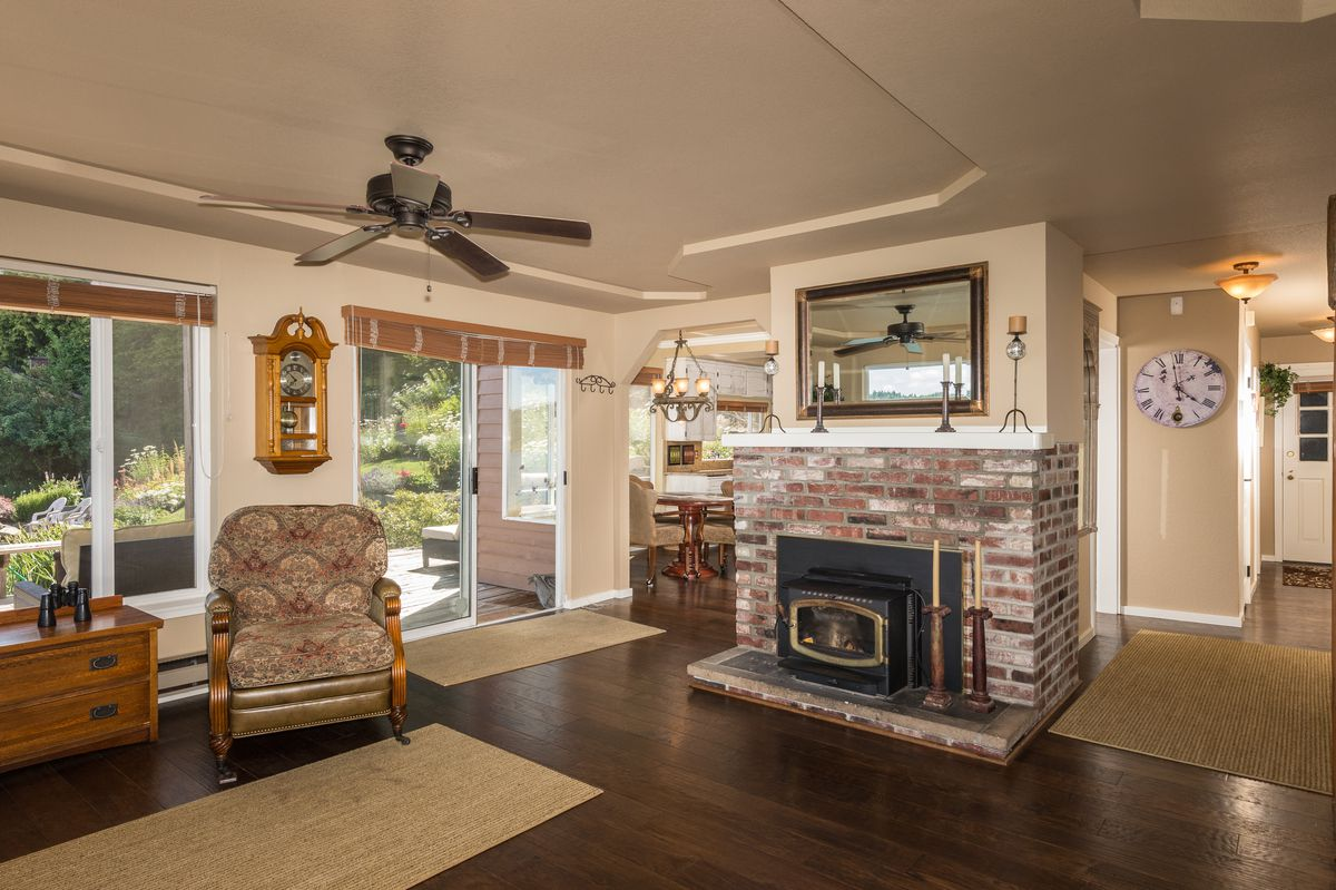 A room with hardwood floors and a wood stove with surrounding brick and a mantle.