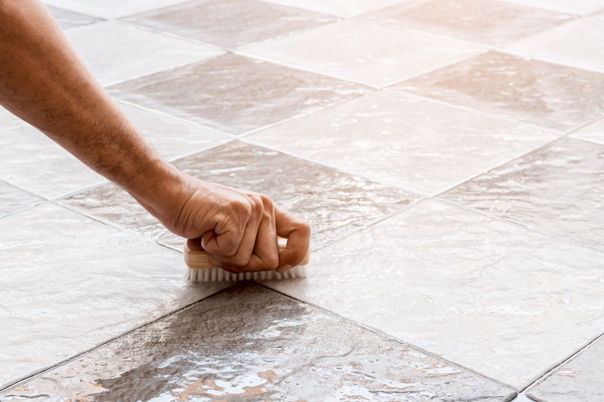 A hand holding a brush, cleaning tile grout.