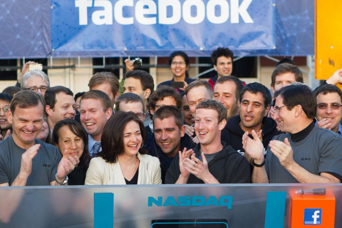 Fans taking pictures with cell phone behind barrier stock photo - Facebook Founder Chairman And Ceo Mark Zuckerbergapplauds At The Opening Bell Of The Nasdaq Stock Market Friday May 18 2012 From Facebook Headquarters