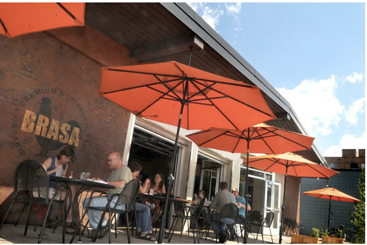 An adobe-colored facade of Brasa St. Paul is shown on a sunny day with the windows open and patio tables set outside