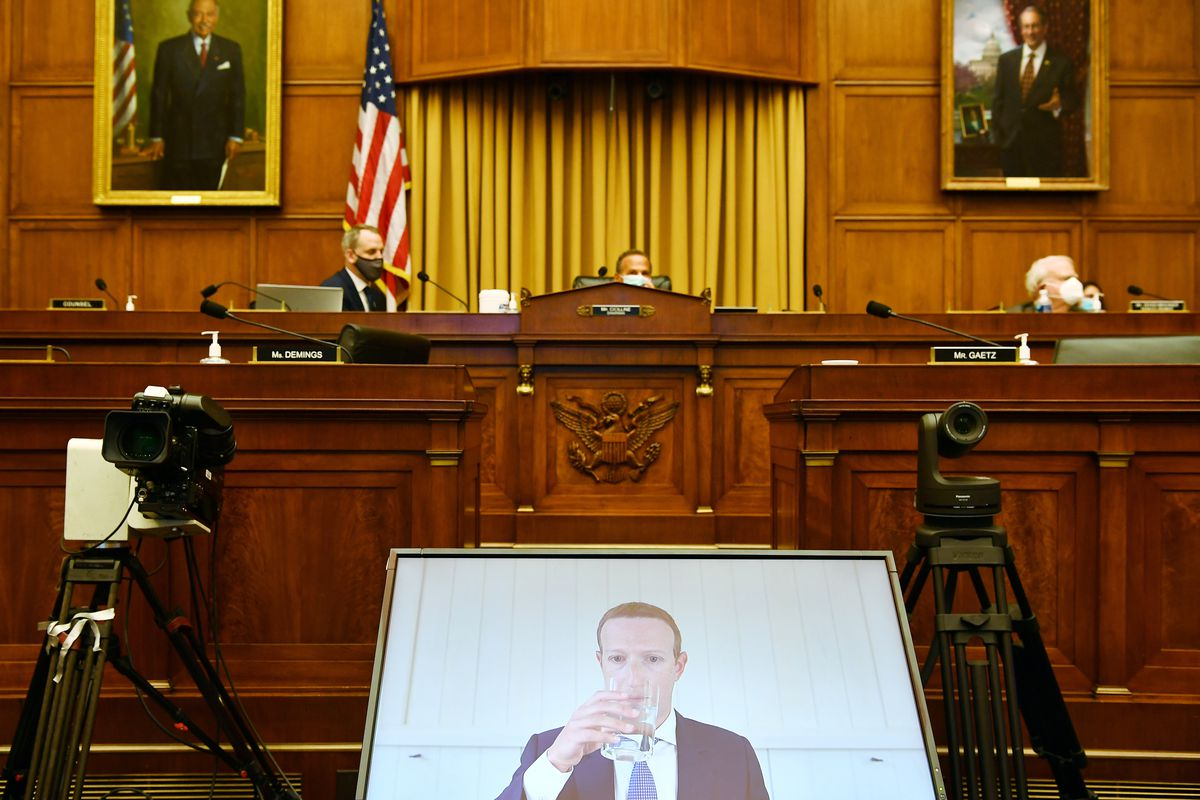 A screen displaying Mark Zuckerberg's face is set up in front of Congress members as part of a congressional hearing.