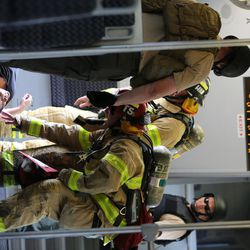 Firefighters check a victim as officials conduct the terrorist attack protection and response drill ÒHell on WheelsÓ at the Salt Lake City Central station, the drill simulates multiple terrorists entering the Salt Lake Valley and dividing up on Tuesday, Aug. 8, 2017.