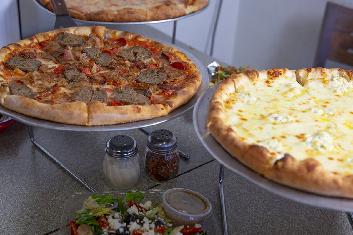 A sausage pizza and a white pie cooling on stands at the original home of Those Guys Pies.