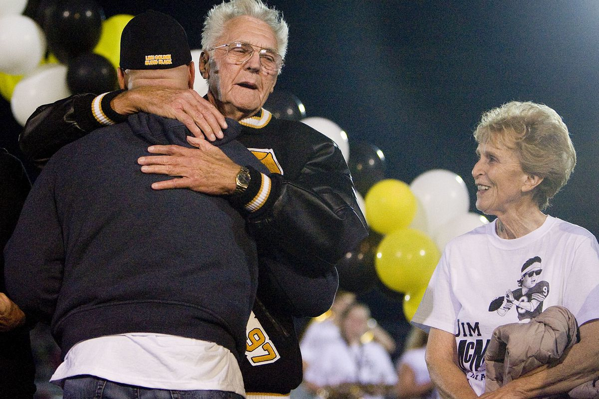 Former Roy High, BYU and NFL football player Jim McMahon hugs his former basketball coach Ted Smith during halftime at Roy High School in Roy, Utah, on Friday, Sept. 16, 2011.
