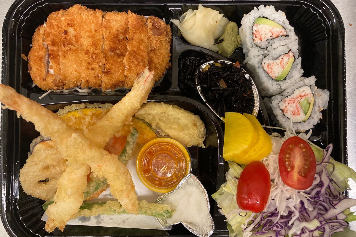 A bento lunch with tempura, tonkatsu, sushi rolls, and salad