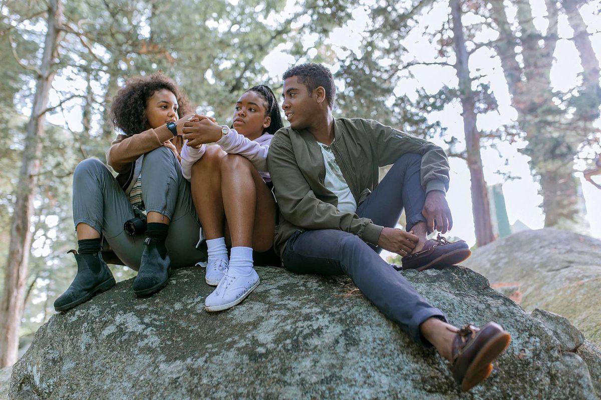 Celeste O'Connor, Lovie Simone, and Jharrel Jerome sit on a rock in a park