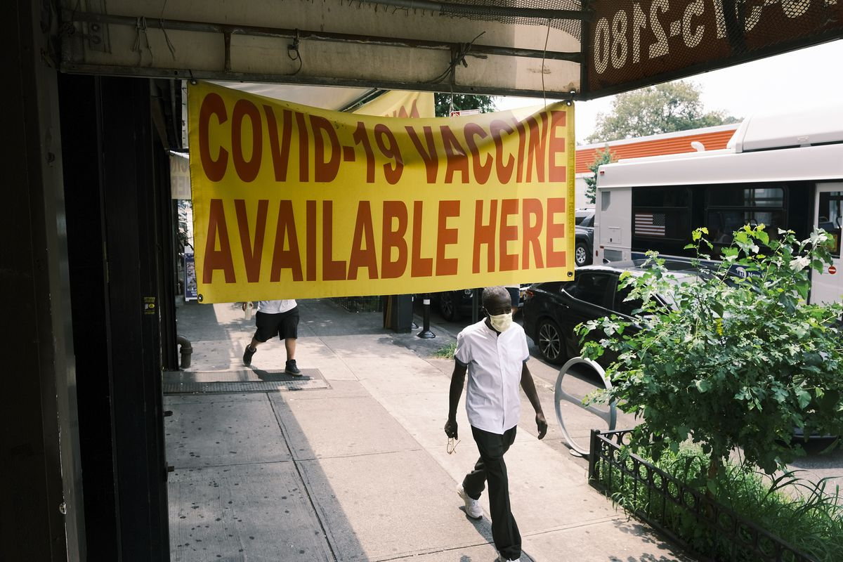 """A sign outside a pharmacy reads """"Covid-19 vaccine available here."""""""