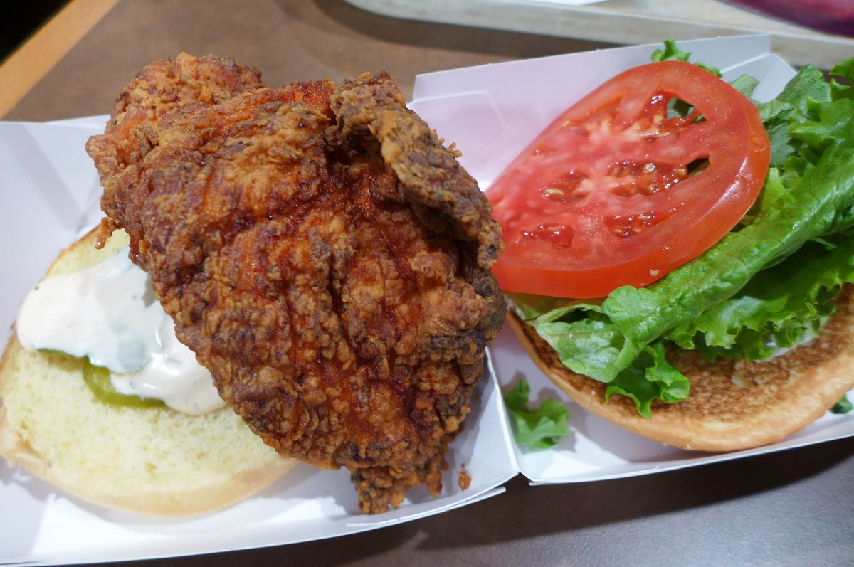 A darkly fried chicken filet on a round bun held open to show the contents, which also includes a schmear of mayo and a pickle chip.