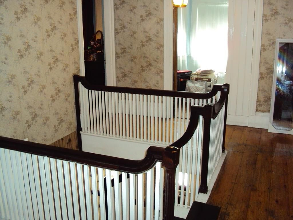 The top of a set of stairs, with doors leading off the hallway.
