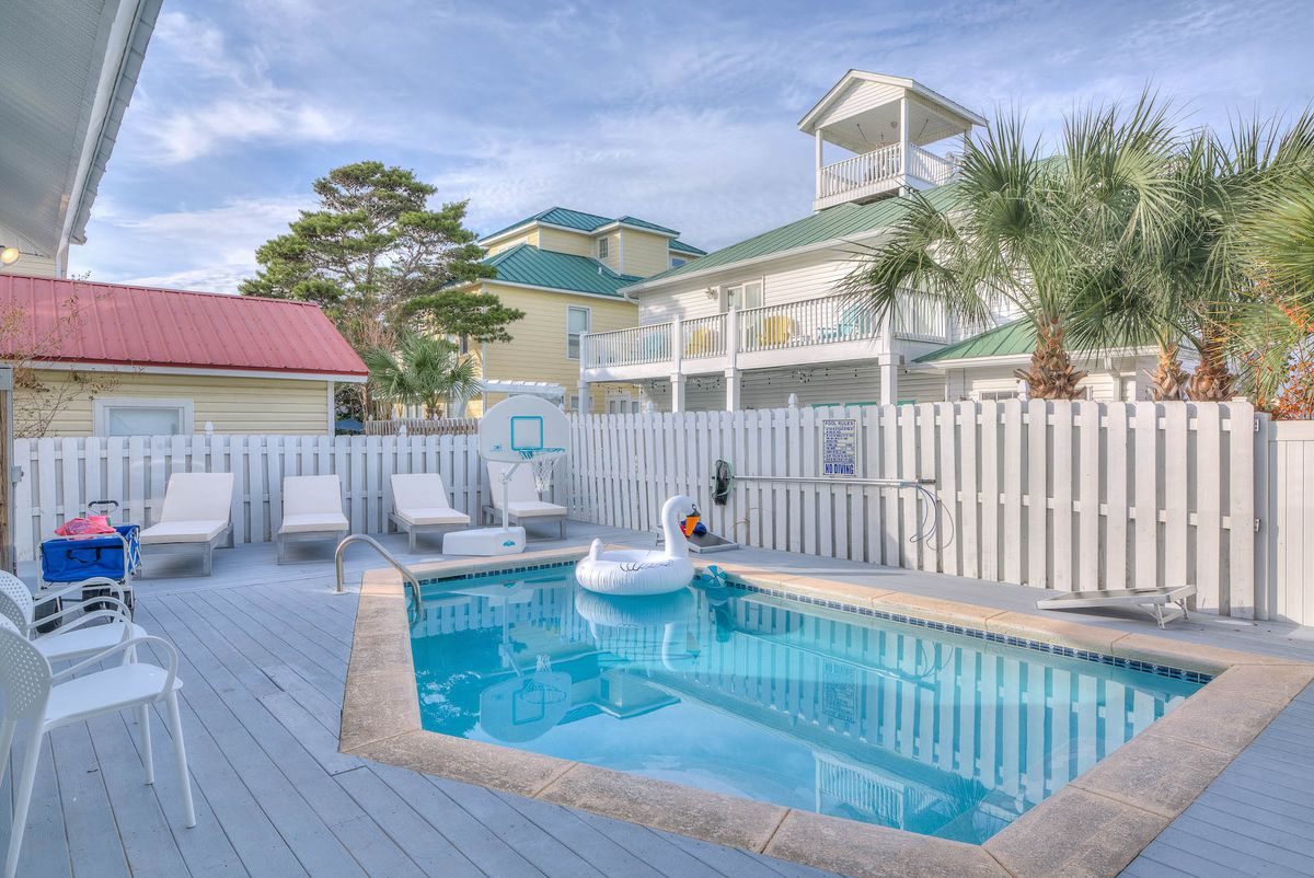 A pool and deck, ringed by a white picket fence, at a high-end short-term rental in Florida.