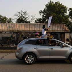 A vehicle with activists holding up Black Lives Matter signs drives by a burned out business on 60th Street in Kenosha, during a protest over the shooting of Jacob Blake, Tuesday, Aug. 25, 2020.